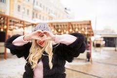 Positives blondes vorbildliches Herstellungsherzsymbol mit ihren Händen an Stockfotografie