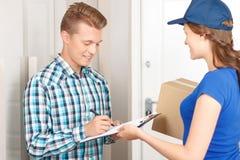 Positives deliverywoman, das Paket liefert Stockfotos