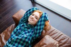 Positives entspanntes Rothaarigemädchen, das auf brauner Ledercouch stillsteht Lizenzfreie Stockfotografie