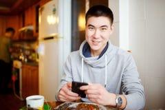 Positives Gefühl eines jungen Mannes, der in der Küche während des Frühstücks sitzt, hält in seinen Händen das Telefon und betrac Lizenzfreie Stockfotografie