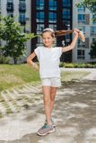 Positives glückliches Mädchen, das ihren Pferdeschwanz hält Lizenzfreie Stockbilder