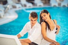 Positives glückliches Paar, das durch den Swimmingpool im Luxussommerferienort sich entspannt Zeit in der Badekurort Wellnessmitt stockbilder