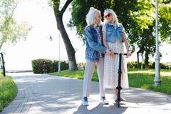 Positives glückliches Paar, das einen Roller reitet lizenzfreie stockfotos