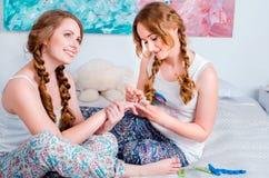 Positives junges Mädchen, das den Spaß zu Hause sitzt auf dem Bett und dem PA hat Stockfotografie