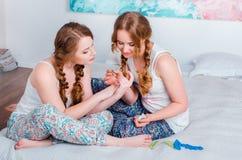 Positives junges Mädchen, das den Spaß zu Hause sitzt auf dem Bett und dem PA hat Stockfotos