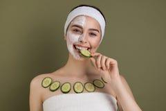 Positives kaukasisches Mädchen des Lächelns mit Lehmmaske und organischen Gurkenscheiben stockfoto