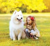 Positives Kind und Hund, die Spaß draußen hat Lizenzfreies Stockfoto