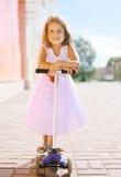 Positives kleines Mädchen, das einen Roller reitet Stockbilder