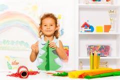 Positives kleines Mädchen, das Karton Weihnachtsbaum hält Lizenzfreies Stockbild