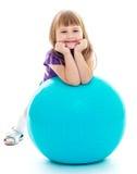 Positives kleines Mädchen mit dem blauen Ball Stockfotos
