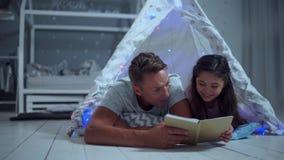Positives kleines Mädchen und ihr Vater, die zusammen ein Buch liest stock footage