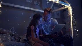 Positives kleines Mädchen, welches das Internet mit ihrem Vater surft stock footage