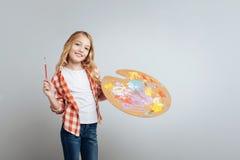 Positives kreatives kleines Mädchen, das geht zu malen Stockbild