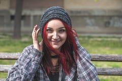Positives l?chelndes obdachloses rotes Haarm?dchen, das auf der Bank auf der Stra?e sitzt und in der Kamera w?hrend sie Spa? habe stockfoto