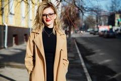 Positives Mädchen auf dem Straßenlächeln Blonde, rote Lippen, beige Mantel, der entlang die Stadtstraße geht Lizenzfreie Stockbilder