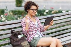 Positives Mädchen, das auf der Bank stillsteht Lizenzfreies Stockbild