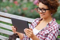Positives Mädchen, das auf der Bank stillsteht Lizenzfreie Stockfotos