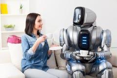 Positives Mädchen, das auf der Couch mit Roboter stillsteht Lizenzfreie Stockfotos