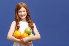 Positives Mädchen, das Früchte hält Stockbilder