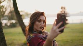 Positives Mädchen, das am Smartphone für selfies im sonnigen Park des Herbstes lächelt und aufwirft stock video