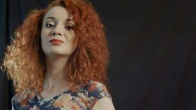 Positives Mädchen mit dem roten Haar auf einem schwarzen Hintergrund stock footage
