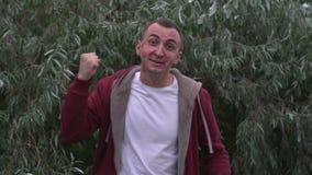 Positives menschliches Gefühl des jungen Mannes mit Gesicht voll von Lippenstiftkennzeichen von Küssen stock video footage