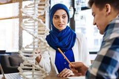 Positives moslemisches Mädchen, das Genetik mit ihrem groupmate studiert lizenzfreie stockfotos