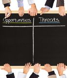 Positives Negatives. Photo of business hands holding blackboard and writing Opportunities and Threats Royalty Free Stock Photos