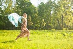 Positives Porträt der lächelnden kaukasischen Frau, die barfüßigoudoors mit fliegendem Halstuch laufen lässt stockfotografie