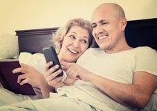 Positives reifes der Paare Social Networking zusammen Stockfoto