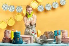 Positives schlaues Mädchen, das einen Plan bildet, wie man nicht die Teller wäscht lizenzfreie stockbilder