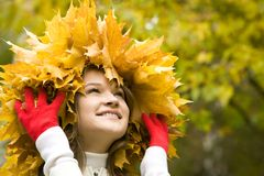 Positivity. Portrait of pretty girl wearing maple wreath and touching it by hands royalty free stock photo