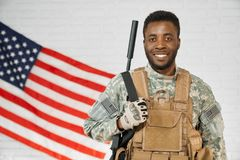 Positivity American soldier wearing army uniform and armour. Portrait of positivity American soldier wearing army uniform and armour smiling at camera. African stock images
