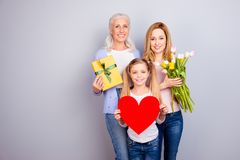 Positivity beauty care trust tenderness concept. Three family sw. Eet cute adorable loving members holding heard package and beautiful flowers cuddling standing Stock Photos