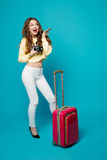 Positivity brunette posing with retro camera and travel bag. Royalty Free Stock Photo