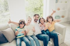 Positivity, careless, carefree four kids and father raised fists. Up, scream loud with wide open mouth sit on soft comfort, cozy couch in light bright living stock photos