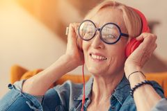 Portrait of cheerful aged woman enjoying the music. Only positivity. Close up of joyful smiling aged woman in headphones listening to music while resting at home royalty free stock photos