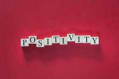 Positivity concept. Positivity word written with wooden blocks stock image