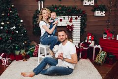 Positivity family posing together near fireplace and presents for Christmas. And happy smiling at camera. Mom holding little son, dad keeping white puppy on royalty free stock photos