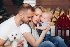 Positivity family posing together near fireplace and presents for Christmas. And happy smiling at camera. Mom holding little son, dad keeping white puppy on stock image