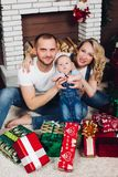 Positivity family posing together near fireplace and presents for Christmas. And happy smiling at camera. Mom holding little son, dad keeping white puppy on royalty free stock photo