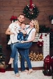 Positivity family posing together near fireplace and presents for Christmas. And happy smiling at camera. Mom holding little son, dad keeping white puppy on stock photos