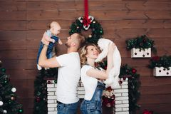 Positivity family posing together near fireplace and presents for Christmas. And happy smiling at camera. Mom holding little son, dad keeping white puppy on royalty free stock photography