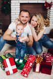 Positivity family posing together near fireplace and presents for Christmas. And happy smiling at camera. Mom holding little son, dad keeping white puppy on stock photography