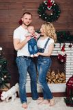 Positivity family posing together near fireplace and presents for Christmas. And happy smiling at camera. Mom holding little son, dad keeping white puppy on stock images
