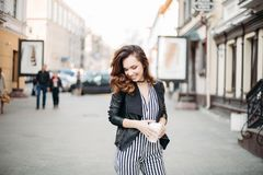 Positivity fashionable brunette in striped dress posing at street. Positivity smiling brunette girl in striped dress and leather jacket posing at camera royalty free stock photo