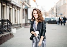 Positivity fashionable brunette in striped dress posing at street. Positivity smiling brunette girl in striped dress and leather jacket posing at camera stock photo