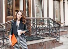 Positivity fashionable brunette in striped dress posing at street. Positivity smiling brunette girl in striped dress and leather jacket posing at camera royalty free stock photography
