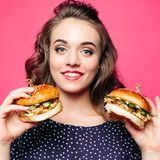 Positivity girl smiling and posing with two tasty humburgers. Beautiful positivity girl smilingat camera and posing with two tasty humburgers. Young pretty royalty free stock photo