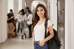 Positivity and happy female student with backpack. Positivity and happy female student with backpack standing on corridor of luxury international university stock image